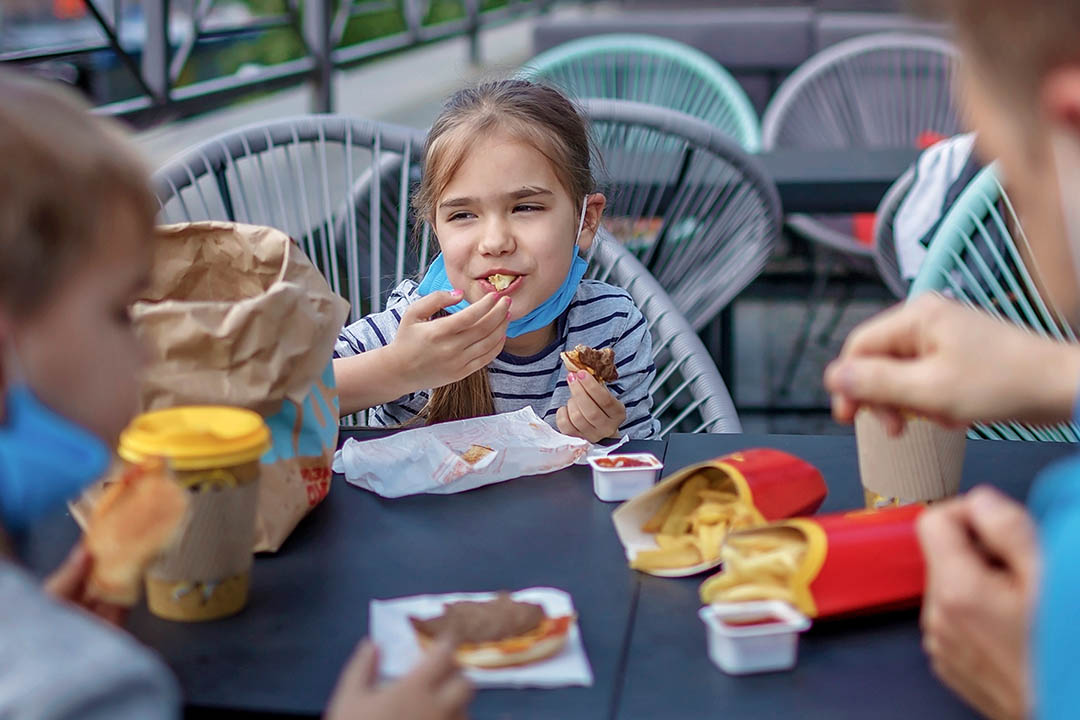 Picture of a young child with friends eating fast food